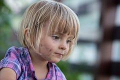 Kaukasisches blondes Mädchen des jungen Babys mit schmutzigem Gesichtsporträt an ihrem städtischen Gemüsegarten der Familie Lizenzfreie Stockfotografie