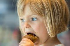 Kaukasisches blondes Mädchen des jungen Babys, welches das Hörnchen im Freien isst Stockfotografie