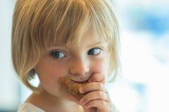 Kaukasisches blondes Mädchen des jungen Babys, welches das Hörnchen im Freien isst Lizenzfreies Stockbild