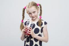 Kaukasisches blondes Mädchen mit den Zöpfen, die in der Polka Dot Dress Against White aufwerfen Stockbild