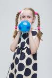 Kaukasisches blondes Mädchen mit den Zöpfen, die in der Polka Dot Dress Against White aufwerfen Stockfoto