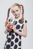 Kaukasisches blondes Mädchen mit den Zöpfen, die in der Polka Dot Dress Against White aufwerfen Lizenzfreie Stockfotografie