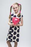 Kaukasisches blondes Mädchen mit den Zöpfen, die in der Polka Dot Dress Against White aufwerfen Lizenzfreies Stockfoto