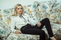Kaukasisches blondes Modell der schönen jungen Mode, das auf Sofa aufwirft Stockbild