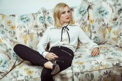 Kaukasisches blondes Modell der schönen jungen Mode, das auf Sofa aufwirft Lizenzfreie Stockfotografie