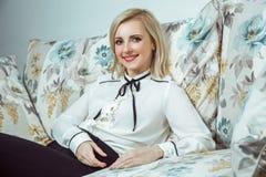 Kaukasisches blondes Modell der schönen jungen Mode, das auf Sofa aufwirft Lizenzfreies Stockfoto