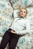 Kaukasisches blondes Modell der schönen jungen Mode, das auf Sofa aufwirft Lizenzfreie Stockbilder