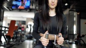 Kaukasisches brunette Mädchen in den schwarzen Gamaschen und im Spitzenhandelnrudersport auf dem Simulator Frau, die Rudermaschin stock video footage