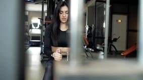 Kaukasisches brunette Mädchen in den schwarzen Gamaschen und im Spitzenhandelnrudersport auf dem Simulator Rückenübungen in der T stock video