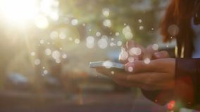 Kaukasisches Frauenholding smatphone auf strett am sonnigen Tag mit heller Blasenanimation erscheint langsam stock footage