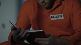 Kaukasisches Gefangenlesebuch in der Zelle, Ausbildung während der Gefängnisstrafe, Nahaufnahme stock video footage