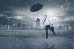 Kaukasisches Geschäftsmannfliegen mit einem Regenschirm Lizenzfreie Stockfotos