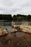 Kaukasisches jugendlich Mädchen in Fluss im weißen Trikotanzug von der Rückseite Lizenzfreies Stockbild
