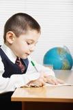 Kaukasisches Jungenschreiben am Schreibtisch sideview stockfoto