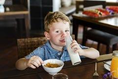 Kaukasisches Kind, das allein frühstückt Lizenzfreies Stockfoto