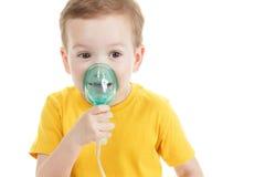 Kaukasisches Kind, welches das Sauerstoff- oder Inhalatorkennzeichen lokalisiert auf Weiß hält stockfotos