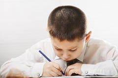 Kaukasisches Kinderschreiben am Schreibtisch lizenzfreies stockfoto