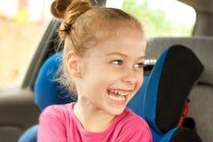 Kaukasisches lachendes Kindermädchen beim Reisen in einen Autositz Stockbilder