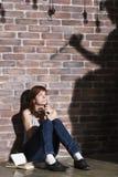 Kaukasisches Mädchen, das auf dem Boden liest einen Horror oder furchtsames ein Thrillerbuch sitzt Drastische Beleuchtung mit Mäd Stockbild