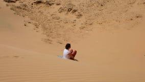 Kaukasisches Mädchen, das ausrichtet, um auf Sand mit Brett zu schieben Lustiger extremer Einstieg auf roter Düne in Muine stock video