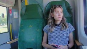 Kaukasisches Mädchen in den Zugreisen eines Hutes Sie ist im Zug allein Langsame Bewegung stock video