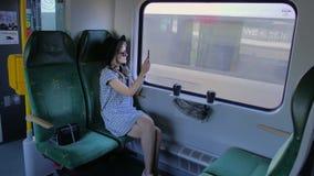 Kaukasisches Mädchen in einem Hut reist in einen Zug Macht Fotos der Natur auf einem mobilen Smartphone Langsame Bewegung stock video