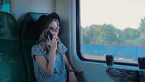 Kaukasisches Mädchen in einem Hut sprechend am Telefon im Zug Sie ist ein erklärt glücklich der anderen Partei Langsame Bewegung stock footage