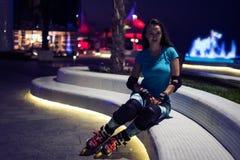 Kaukasisches Mädchen genießt Rollschuhlaufen an der Nachtstadt mit Lichtern im bokeh Lizenzfreie Stockfotografie