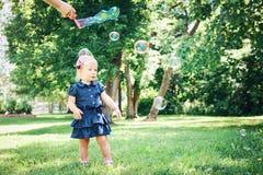 Kaukasisches Mädchenkind im blauen Kleid, das draußen im Feldwiesenpark, Seifenblasen machend steht Lizenzfreies Stockfoto
