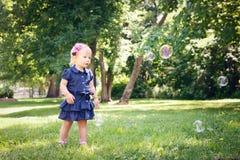 Kaukasisches Mädchenkind im blauen Kleid, das draußen im Feldwiesenpark, Seifenblasen machend steht Stockbilder