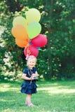 Kaukasisches Mädchenkind im blauen Kleid mit bunten Ballonen, im Feldwiesenpark Stockfotos