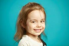 Kaukasisches nettes Lächeln des kleinen Mädchens, Nahaufnahmeporträt des schönen Kindes auf blauem lokalisiertem Hintergrund lizenzfreie stockfotografie