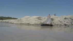 Kaukasisches Rothaarigemädchen im blauen Bikini schiebt unten einen Schlammhügel und -plumpse in Vulkan Shugo stock video footage