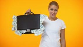 Kaukaska żeńska pokazuje teczka dolary pełno, rynek papierów wartościowych inwestycja zbiory