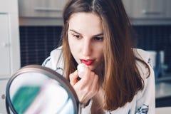 Kaukaska biała dziewczyny kobieta w bieliźnie robi jej makeup przed lustrem w ranku w domu Zdjęcia Stock