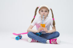 Kaukaska Blond dziewczyna jest ubranym naliczka obsiadanie na podłoga z filiżanką sok i Pije Przez słomy Fotografia Stock