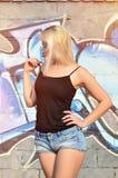 Kaukaska blondynki dziewczyna w drelichów skrótach i czarnym podkoszulku bez rękawów pozuje przeciw graffiti ścianie fotografia stock
