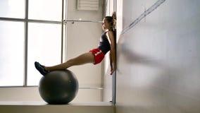 Kaukaska brunetka w sportswear ćwiczenia z gimnastyczną piłką zbiory