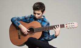 Kaukaska chłopiec bawić się na gitarze akustycznej Zdjęcia Royalty Free