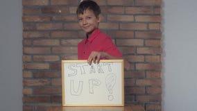 Kaukaska chłopiec mienia pastylka z handwriting słowa rozpoczęciem obraz royalty free