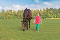 Kaukaska chłopiec prowadzi w okazji wysoki koń na z włosami zieleni polu w słonecznym dniu Na tle las, zdjęcie stock