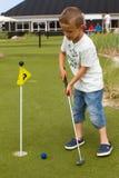 Kaukaska chłopiec przy mini polem golfowym fotografia stock