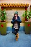 Kaukaska dziewczyna na zima dniu pozycja modlitwa, medytacja, dziwaczna na zewnątrz Wschodnio-azjatycki Buddyjskiej świątyni obraz stock