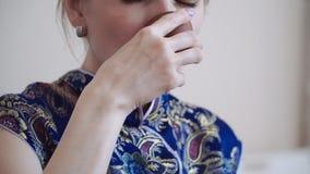 Kaukaska dziewczyna w błękitnej żyłkowanej smokingowej napój herbacie i cieszy się fragrant herbaty od filiżanki zdjęcie wideo