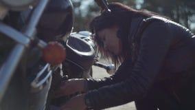 Kaukaska dziewczyna załatwia jej sprawdza warunek w miękkim świetle w górę lub motocykl Hobby, podróżować i aktywny styl życia, zbiory