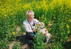 Kaukaska kobieta bawić się z jej psem w trawie zdjęcie royalty free