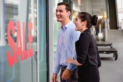 Kaukaska kobieta i mężczyzna excited gdy zobaczy metkę na sprzedaży przy sklepem Fotografia Royalty Free