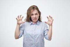 Kaukaska kobieta pokazuje jej dziką stronę pozuje w błękitnej koszula warczy przy tobą i gestykuluje pazura kształt z ona ręki zdjęcie stock
