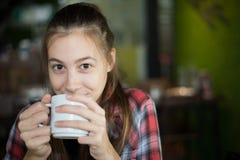 Kaukaska kobieta trzyma filiżankę kawy w jej ręce na zamazanym tle Obraz Stock