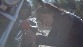 Kaukaska kobieta załatwia jej sprawdza warunek w miękkim świetle w górę lub motocykl Hobby, podróżować i aktywny, zdjęcie wideo